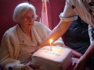 Photograph of elderly person receiving birthday cake